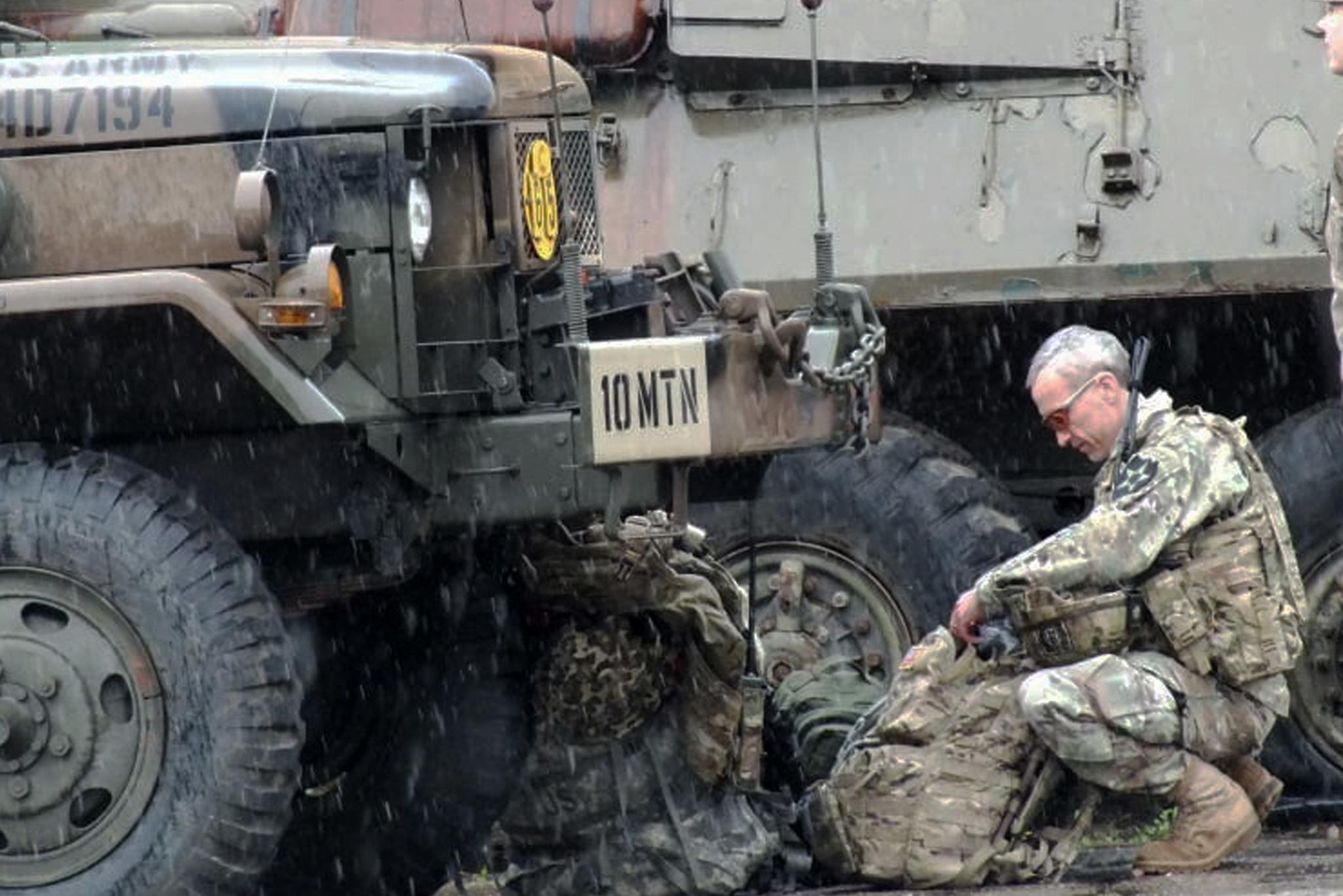 Major Syka se při deštivé akci připravuje pro následující úkoly.